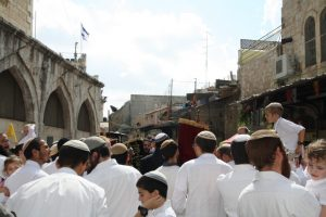 Orthodox Jews dressed in white dance with Torahs on Simchat Torah, in Jerusalem's Old City, Muslim Quarter, on the Via Dolorosa. (Photo by Lynne Golodner)