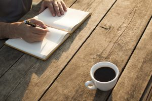 Man Writing Notes on wooden table