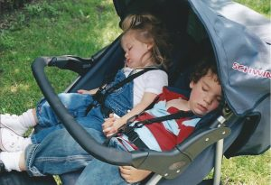 Eliana and Asher asleep in the stroller years ago, their hands clasped.