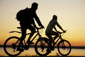 Young couple riding bicycles at sunset.
