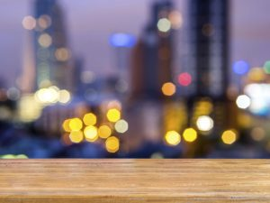 Rustic wooden planks over abstract bokeh cityscape night backgro